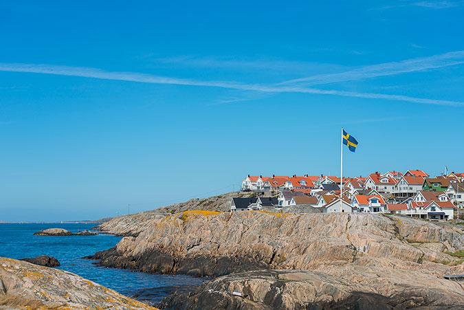 Bebyggelse på en kal klippö i skärgården. Blått hav, blå himmel och en flaggstång med svenska flaggan.