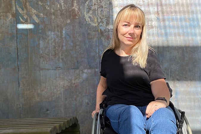 porträtt av Pia Hammagren. Hon sitter i en rullstol framför en spräcklig betong- eller möjligen stenvägg.