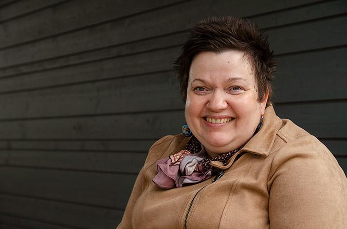 Porträtt av Sari Nykvist. Sari ler mot kameran. Hon bär en brun jacka och en scarf.