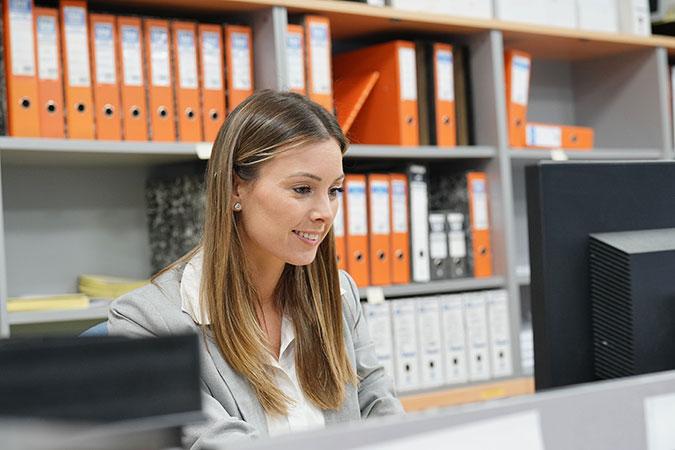 En kvinna sitter bakom en datorskärm och jobbar. I bakgrunden en hylla fylld med pärmar.