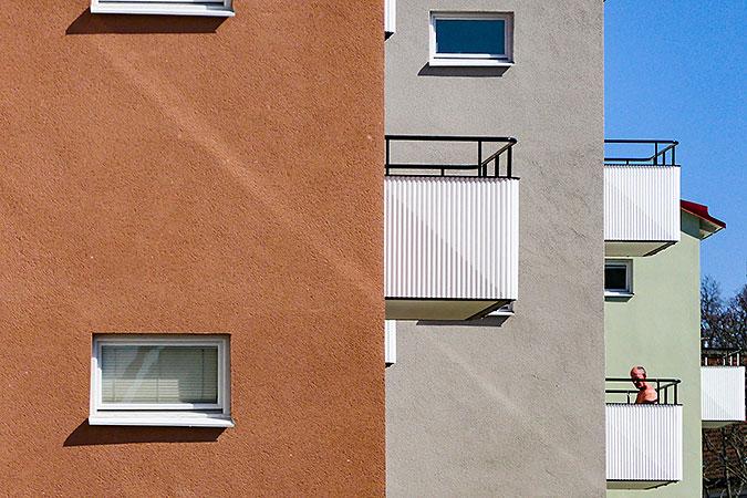 putsade flerfamiljshus i tre färger. Ett rätt, ett grått och ett grönt. Alla har vita balkonger. PÅ en av dessa sitter det en man.