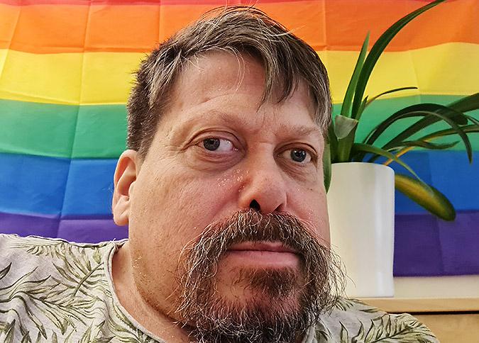 Porträttfoto av Patrik Forslin. En korthårig man med skägg som poserar framför en regnbågsflagga och en krukväxt.