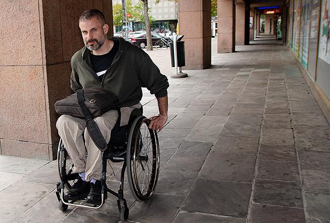 Rasmus Isaksson rullar i sin rullstol i en arkad utanför en byggnad.