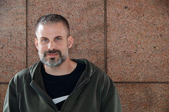Rasmus Isaksson fotograferad mit en stenklädd vägg.