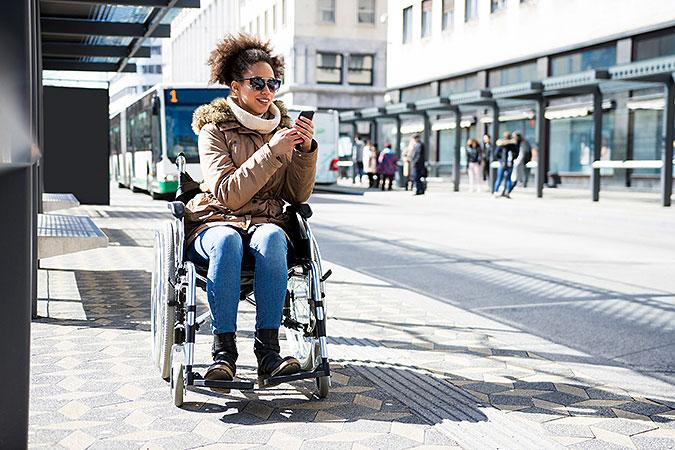 Kvinna sitter i rullstol på en busshållplats. I handen håller hon en mobiltelefon som hon gör något spännande med. I bakgrunden kommer bussen.