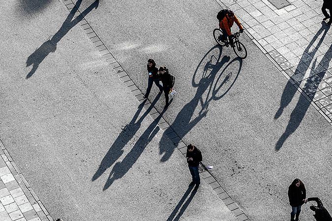 En gata sedd uppifrån. Några fotgängare och en cyklist kastar långa skuggor på asfalten.