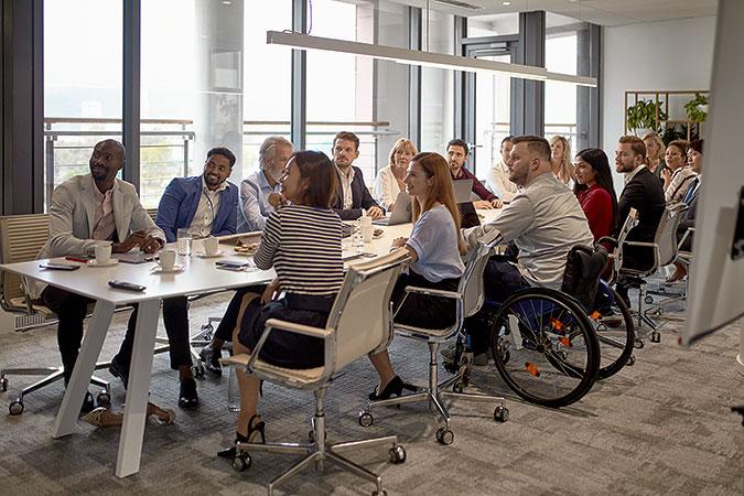 Ett dussin personer sitter i möte runt ett bord i ett konferensrum. De har sin uppmärksamhets riktad mot någon utanför bilden. En av personerna använder rullstol.