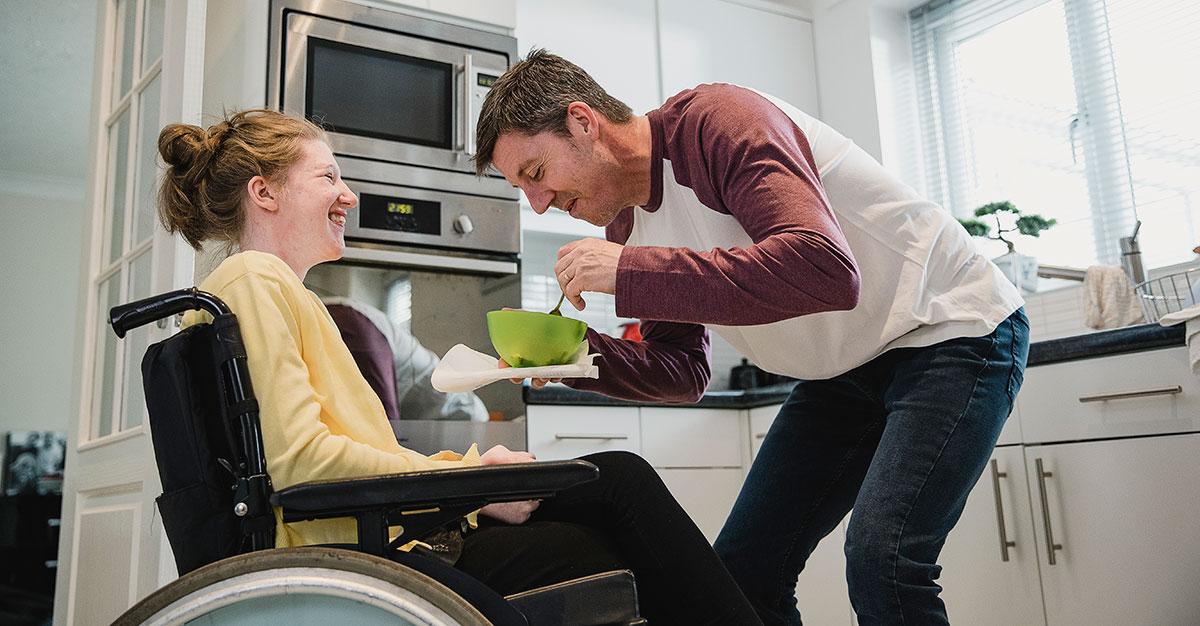 En man hjälper en yngre kvinna med maten i ett kök.